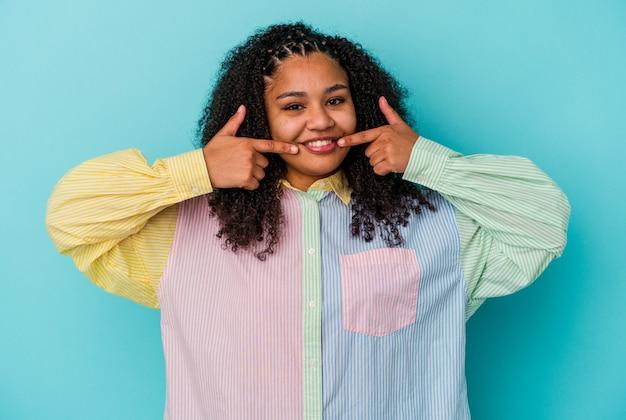 Jovem afro-americana isolada em uma parede azul sorrindo, apontando o dedo para a boca
