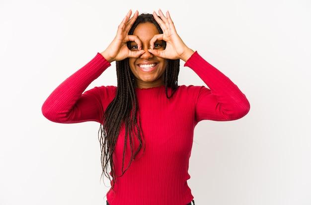 Jovem afro-americana isolada mostrando sinal de aprovação sobre os olhos