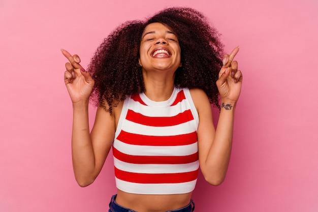 Jovem afro-americana isolada no rosa cruzando os dedos por ter sorte