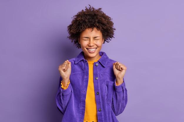 Jovem afro-americana muito feliz e positiva ergue os punhos cerrados e celebra algo com triunfo vestida com uma jaqueta da moda