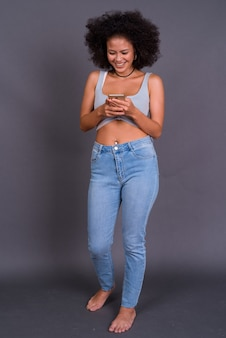 Jovem afro-americana multiétnica com cabelo afro contra uma parede cinza