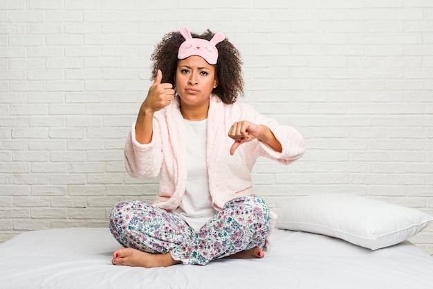 Jovem afro-americana na cama com pijama mostrando os polegares para cima e para baixo
