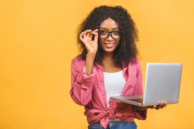 Jovem afro-americana negra positiva e legal com cabelo encaracolado, usando laptop e sorrindo