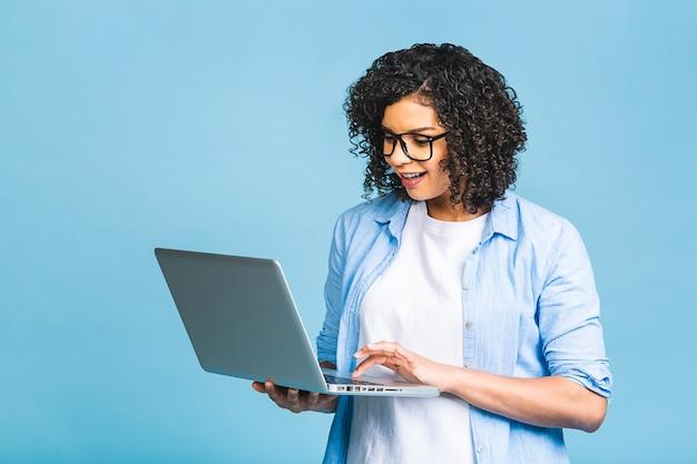 Jovem afro-americana negra positiva legal com cabelo encaracolado, usando laptop e sorrindo isolado sobre fundo azul.