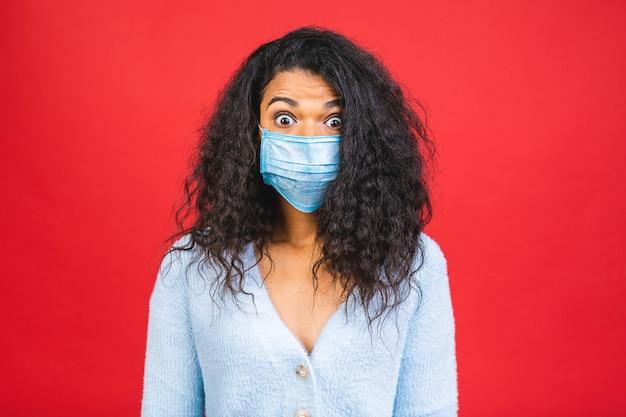 Jovem afro-americana negra usando máscara médica isolada sobre fundo vermelho