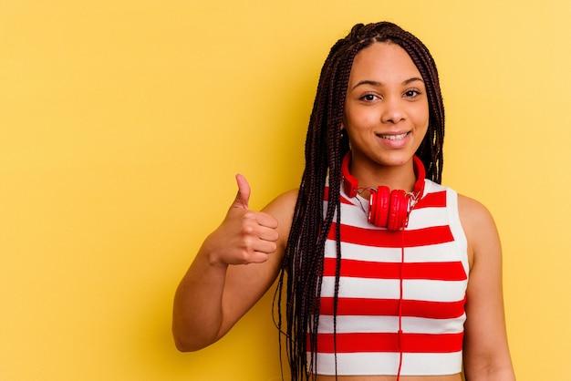 Jovem afro-americana ouvindo música com fones de ouvido isolados em um fundo amarelo, sorrindo e levantando o polegar