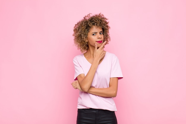 Jovem afro-americana parecendo séria, pensativa e desconfiada, com um braço cruzado e a mão no queixo, opções de ponderação na parede rosa