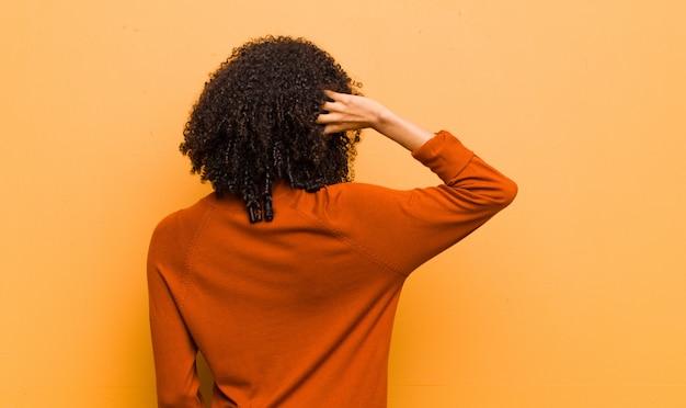Jovem afro-americana posando enquanto coçar o cabelo confuso