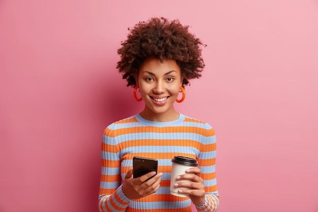 Jovem afro-americana satisfeita e encantadora usa smartphone para comunicação online, pausa para o café, segura o copo de papel na mão e desfruta de bom dia, usa um macacão listrado isolado na parede rosa