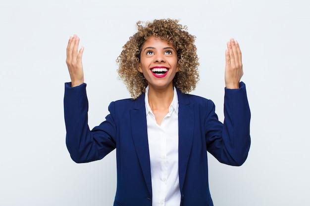 Jovem afro-americana se sentindo feliz, pasma, sortuda e surpresa, comemorando a vitória com as duas mãos para cima na parede plana
