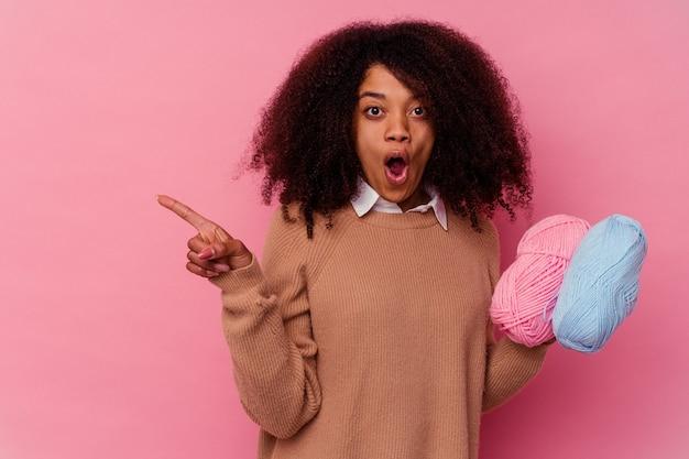 Jovem afro-americana segurando linhas de costura isoladas em um fundo rosa apontando para o lado