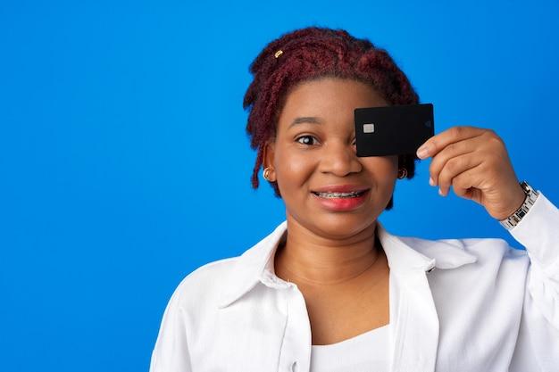 Jovem afro-americana segurando um cartão de crédito preto contra um fundo azul.