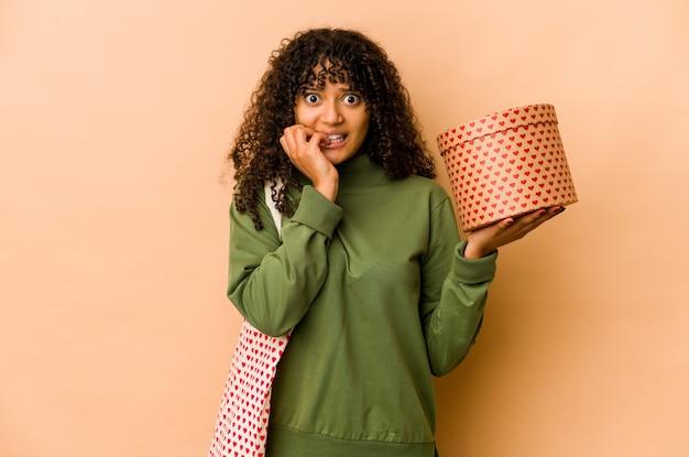 Jovem afro-americana segurando um presente de dia dos namorados, roendo as unhas, nervosa e muito ansiosa.