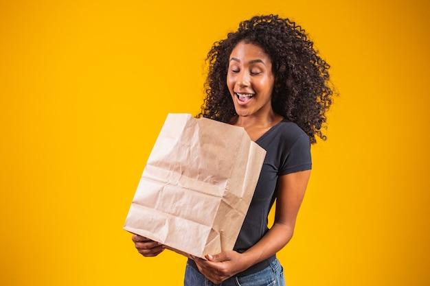 Jovem afro-americana segurando um saco de papel para levar, sorrindo feliz em fundo amarelo