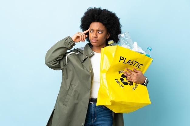 Jovem afro-americana segurando uma sacola reciclada isolada em colorido, tendo dúvidas e pensando