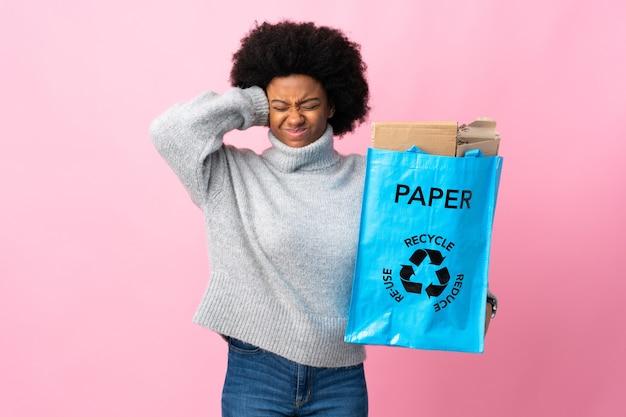 Jovem afro-americana segurando uma sacola reciclável frustrada e cobrindo as orelhas