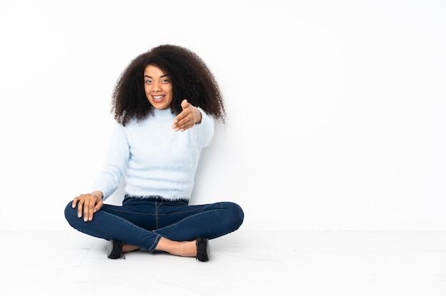 Jovem afro-americana sentada no chão apertando as mãos para fechar um bom negócio