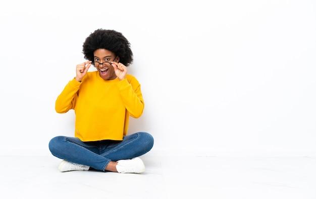 Jovem afro-americana sentada no chão com óculos e surpresa