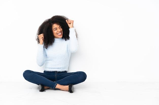 Jovem afro-americana sentada no chão comemorando uma vitória
