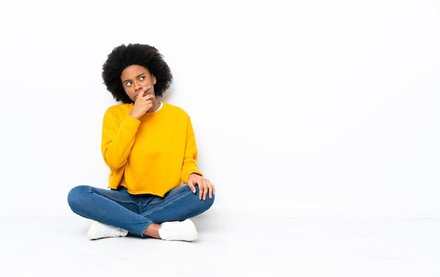 Jovem afro-americana sentada no chão