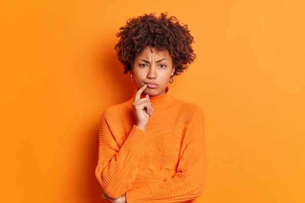 Jovem afro-americana séria e descontente com a testa franzida e o dedo próximo aos lábios