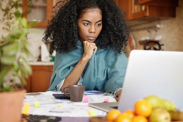Jovem afro-americana séria em um embrulho quente trabalhando nas finanças à noite