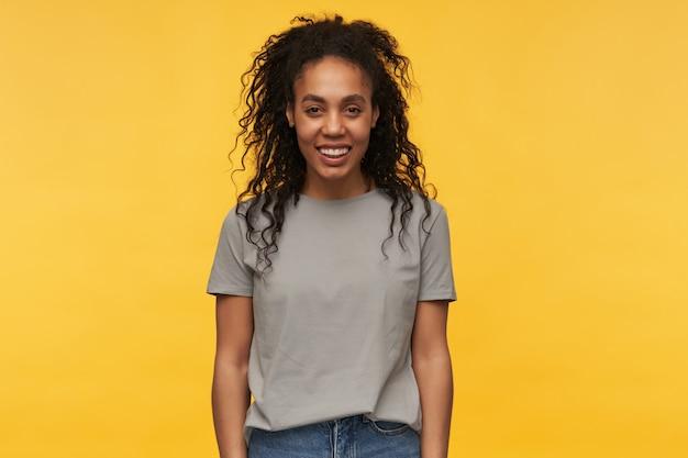 Jovem afro-americana sorri, veste camiseta cinza e calça jeans, mantém as mãos cruzadas