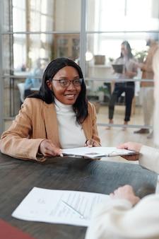 Jovem afro-americana sorridente de óculos, sentada à mesa e dando seu currículo ao gerente de rh durante uma entrevista de emprego