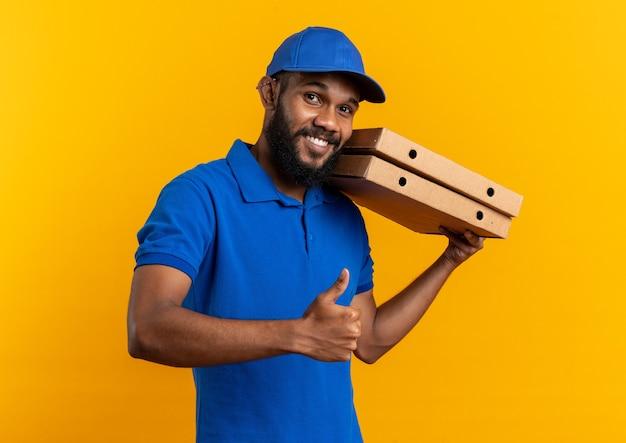 Jovem afro-americana sorridente segurando caixas de pizza e dedilhando isolado em um fundo laranja com espaço de cópia