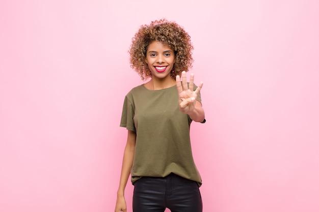 Jovem afro-americana sorrindo e parecendo amigável, mostrando o número quatro ou o quarto com a mão para a frente, em contagem regressiva na parede rosa
