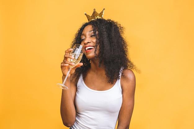 Jovem afro-americana usando coroa de ouro da rainha e bebendo champanhe