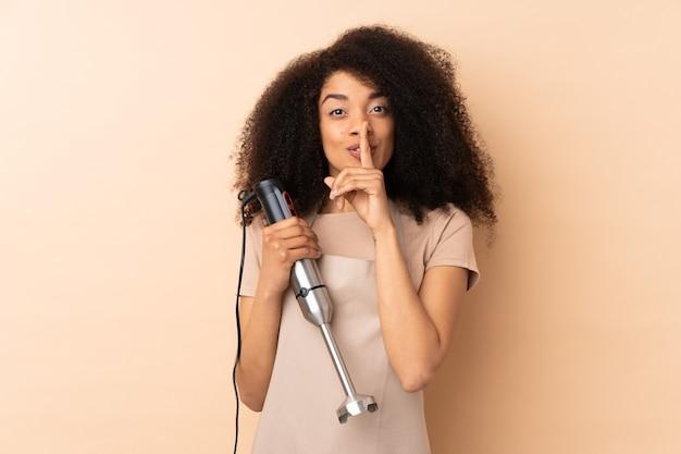 Jovem afro-americana usando um liquidificador isolado em bege, fazendo o gesto de silêncio
