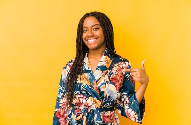 Jovem afro-americana vestindo um pijama asiático, pessoa isolada apontando com a mão para uma camisa cópia espaço, orgulhosa e confiante