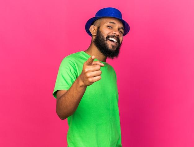 Jovem afro-americano a rir com um chapéu de festa a apontar na frente, isolado na parede rosa