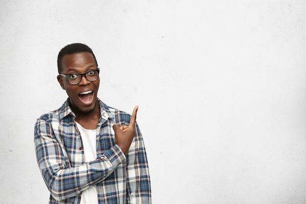 Jovem afro-americano admirado de óculos olhando para a câmera com a boca aberta mostrando os dentes