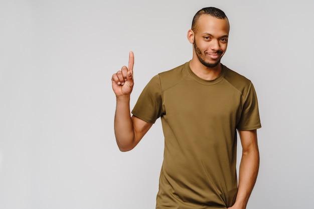 Jovem afro-americano alegre e amigável com uma camiseta verde mostrando um com os dedos