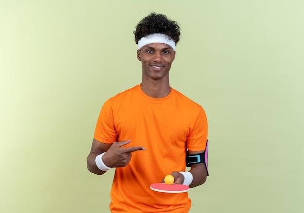 Jovem afro-americano alegre e esportivo usando bandana e pulseira segurando e aponta para a raquete de pingue-pongue com bola isolada no fundo verde