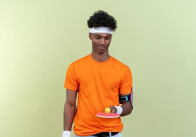 Jovem afro-americano alegre e esportivo usando bandana e pulseira segurando e olhando para a raquete de pingue-pongue com bola isolada no fundo verde