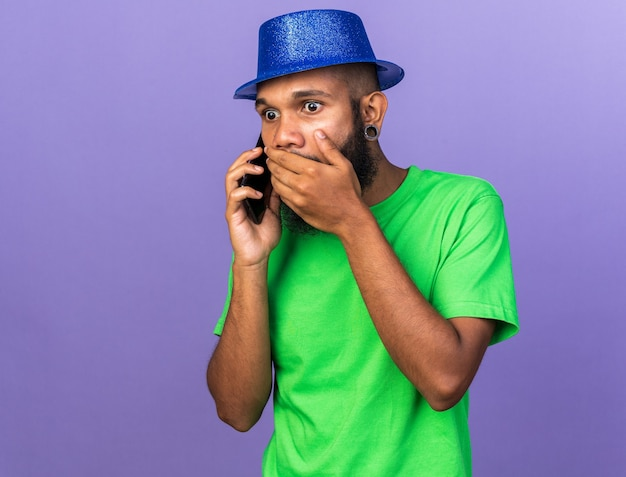 Jovem afro-americano assustado com chapéu de festa falando no telefone tapando a boca com a mão
