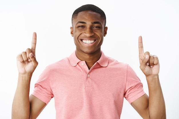 Jovem afro-americano bonito com camiseta polo rosa