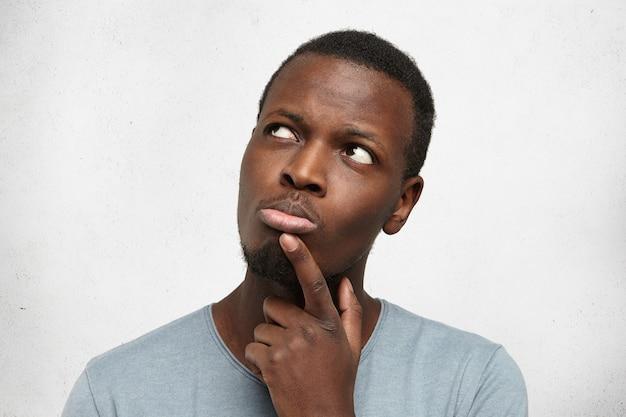 Jovem afro-americano bonito olhando para cima com uma expressão pensativa e cética