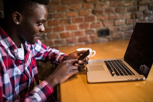 Jovem afro-americano bonito sorrindo alegremente enquanto lê sms no smartphone, manda mensagens usando wi-fi grátis, toma café em um café