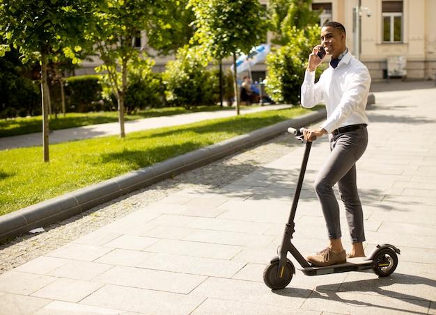 Jovem afro-americano bonito usando um telefone celular em pé com uma scooter elétrica em uma rua