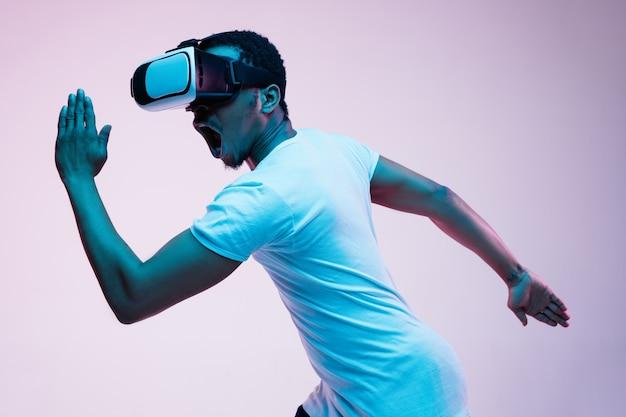 Jovem afro-americano brincando e usando óculos vr em luz de néon em gradiente