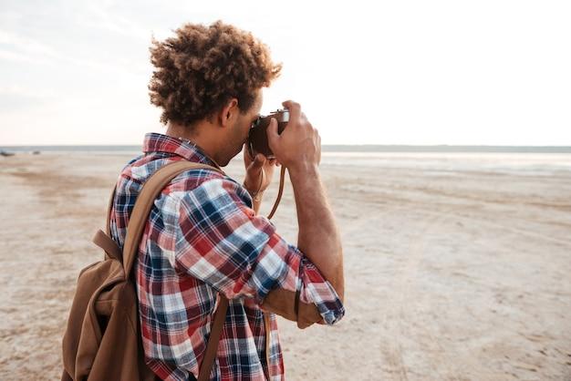 Jovem afro-americano cacheado com uma mochila em pé e tirando fotos na praia