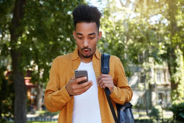 Jovem afro-americano caminhando no parque, veste uma camisa amarela e uma camiseta branca, recebeu uma mensagem de um amigo com uma notícia incrível, parece surpreso com o gadget.
