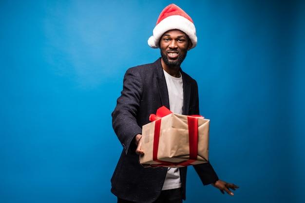 Jovem afro-americano com camisa branca segurando caixas de presente nas mãos