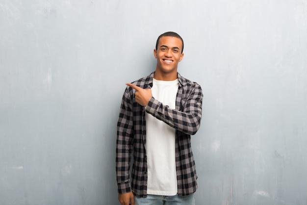 Jovem afro-americano com camisa quadriculada apontando para o lado para apresentar um produto