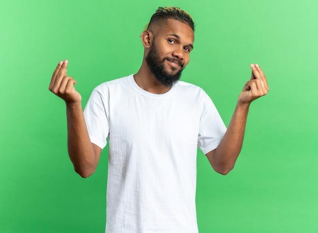 Jovem afro-americano com camiseta branca olhando para a câmera sorrindo, fazendo gesto de dinheiro esfregando os dedos