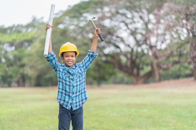 Jovem afro-americano com chapéu de engenheiro segurando um martelo e plantas